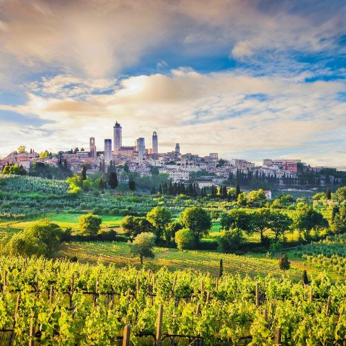 Classic view of the medieval town of San Gimignano and Tuscan countryside in golden evening light at sunset with dramatic clouds province of Siena Tuscany Italy