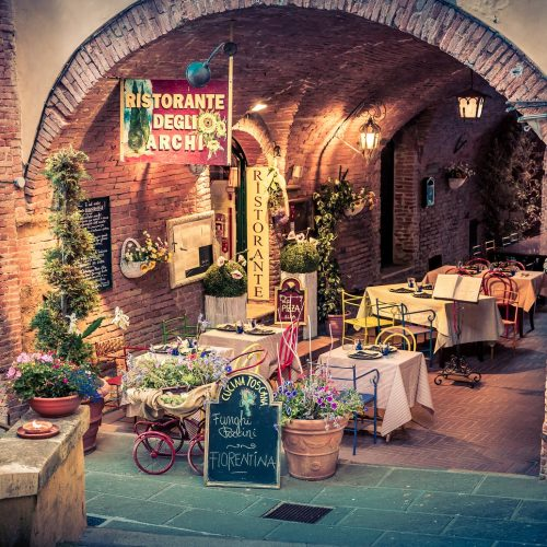 MONTEPULCIANO ITALY - JUNE 25 2015: small pizza restaurant with beautiful flowers decoration in antique Montepulciano city Italy